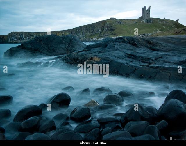 Sea rolling over rocks in front of Dunstanburgh Castke - Stock Image