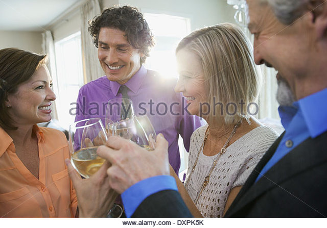 Happy family and friends toasting wine at home party - Stock Image