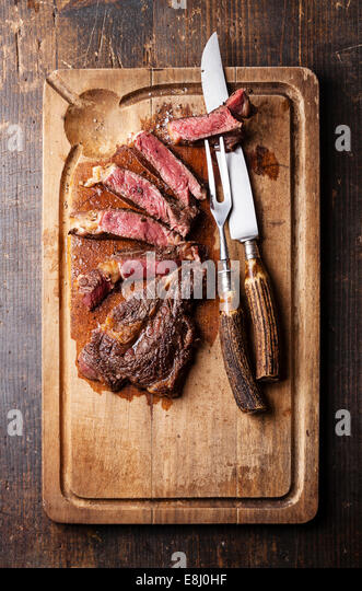 Medium rare Beef steak Ribeye with knife and fork for meat on cutting board on dark wooden background - Stock Image