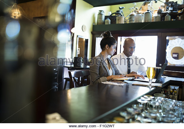 Business people working at laptop in pub - Stock Image