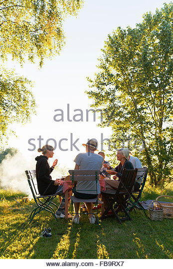 Sweden, Sodermanland, Jarna, Family having dinner in backyard at sunset - Stock-Bilder