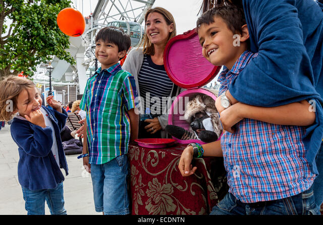 A Family Poses With A Street Entertainer At The South Bank, London, England - Stock Image