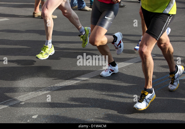 Berlin, Germany, the marathon runners cast their shadows on the road - Stock Image