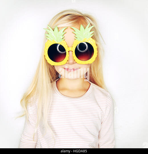 Little adorable girl in pineapple sunglasses smiling and looking at camera on studio background. - Stock Image