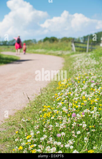 Adult woman and child together on trek, walking down rural gravel road on a warm summer day. - Stock Image