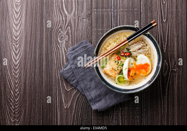 Asian noodles with egg, tofu and enoki in bowl on gray wooden background - Stock Image
