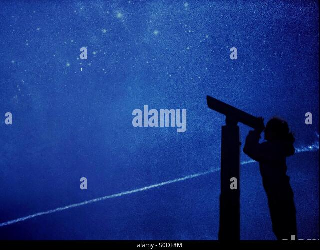 Young girl in silhouette star gazing using telescope - Stock-Bilder