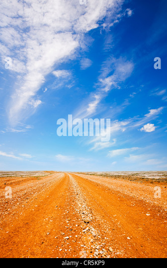 Red dirt road in the Australian outback, under a blazing hot blue sky. - Stock Image