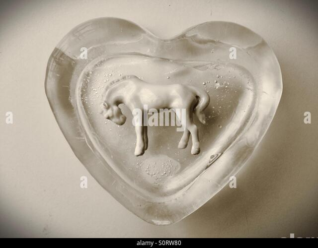 A white horse figurine in an ice block shaped like a heart. - Stock Image