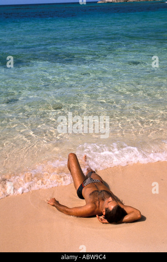 TROPICS Man relaxing at edge of the water - Stock Image