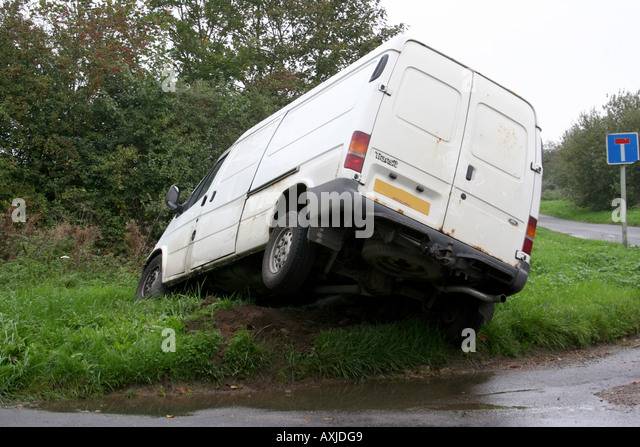 A white van crashed into a ditch. - Stock Image