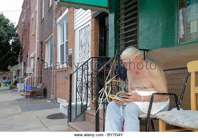 Philadelphia Pennsylvania South Philly sidewalk man senior old barechest sitting reading white hair outdoor row - Stock Image