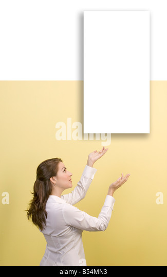 woman shows empty white picture on wall - Stock Image