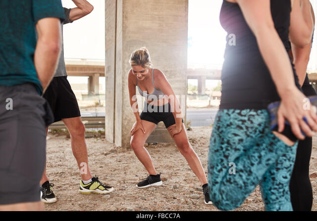 Shot of young woman stretching after a morning run with her friends. Running club group taking break from running - Stock Image