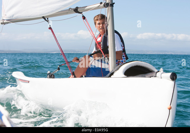 Teenager sailing boat - Stock Image