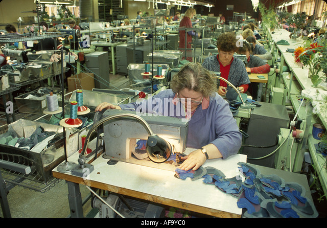 Latvia Riga Pirma Den Athletic Shoes manufacturing joint venture with Germany factory workers sewing machines - Stock Image