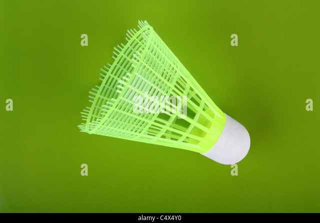 One yellow badminton shuttlecock on a green background - Stock Image