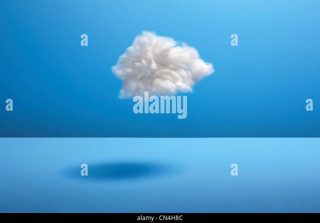Cotton ball cloud against blue backdrop - Stock Image