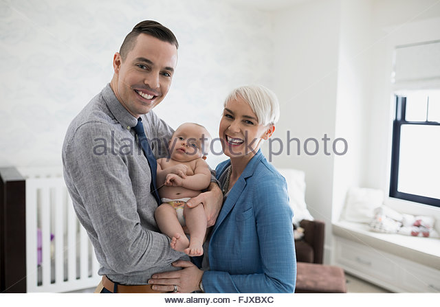 Portrait smiling parents holding baby son in nursery - Stock Image