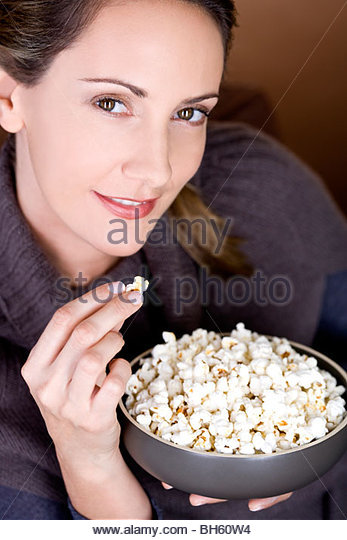 A mid adult woman eating popcorn - Stock-Bilder