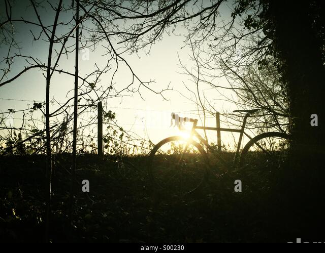 Silhouette of bicycle with Sunrise - Stock Image