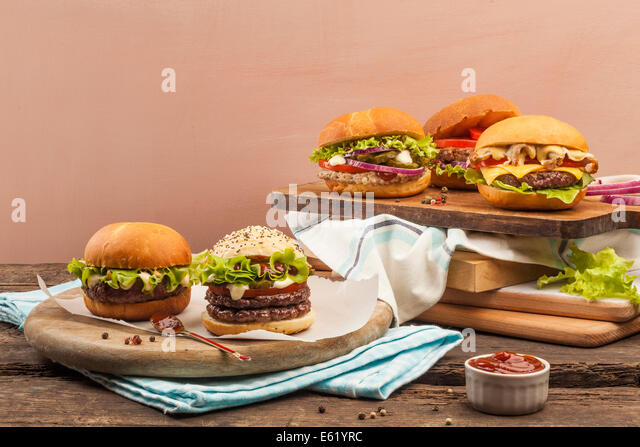 Five different gourmet burgers on wooden background - Stock Image