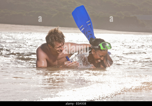Young couple lying in sea, wearing snorkel - Stock Image