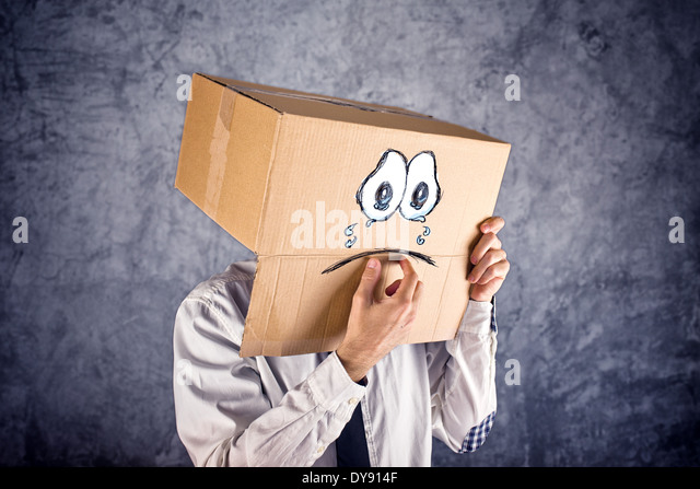 Businessman with cardboard box on his head and sad crying face expression. Concept of sadness and depression. - Stock Image