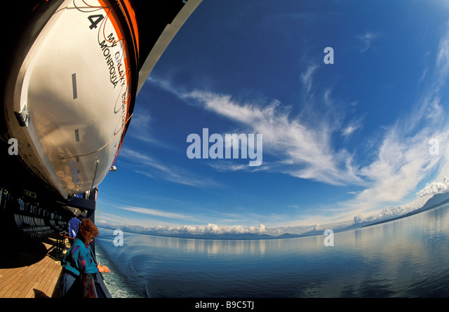 Alaska Cruise Inside Passage sunny fisheye view cruise ship water life boatsnow capped mountains woman passenger - Stock Image