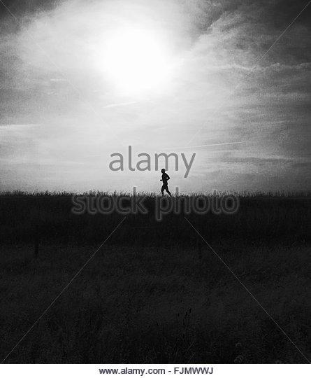 Silhouette Man Running On Grassy Field Against Sky - Stock-Bilder
