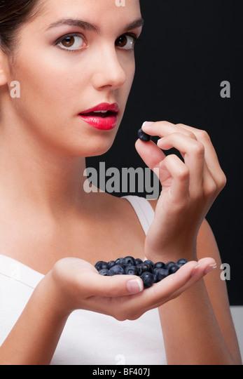 Close-up of woman eating blueberries - Stock-Bilder