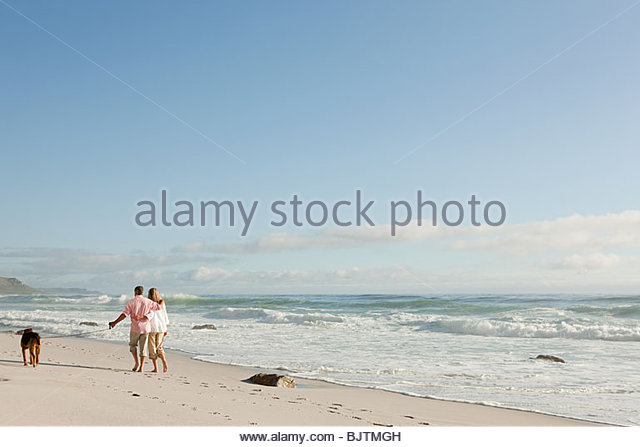 Couple walking dog by the sea - Stock Image