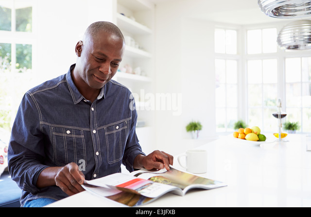 African American Man Reading Magazine At Home - Stock Image