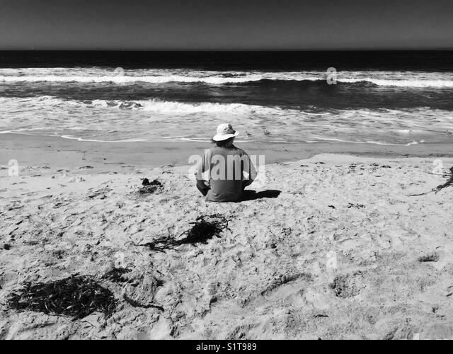 Man sitting on beach - Stock Image