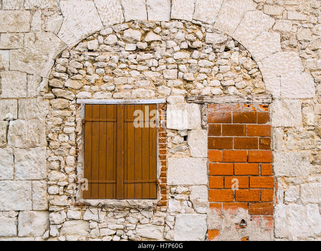 Blocked doorway and window under stone arch - France. - Stock Image
