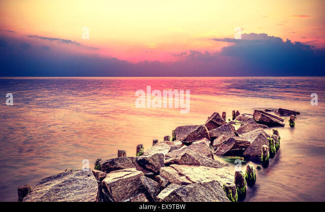 Purple sunset over beach, peaceful sea landscape. - Stock Image