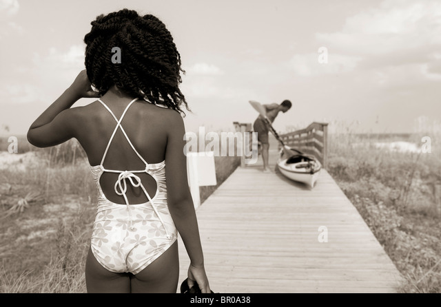 African American girl in swimming suit on Florida beach boardwalk with kayak and father - Stock Image