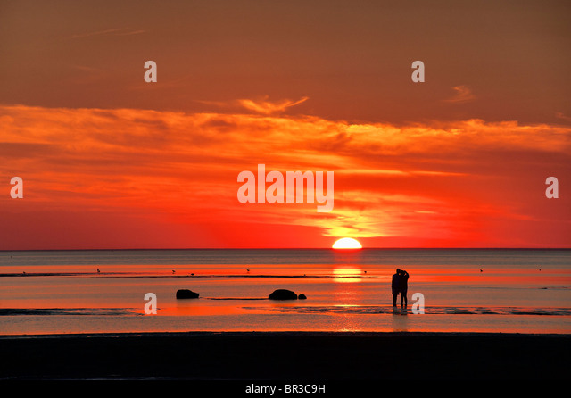 Couple watches sunset together, Skaket beach, Cape Cod, MA, Massachusetts, USA - Stock Image