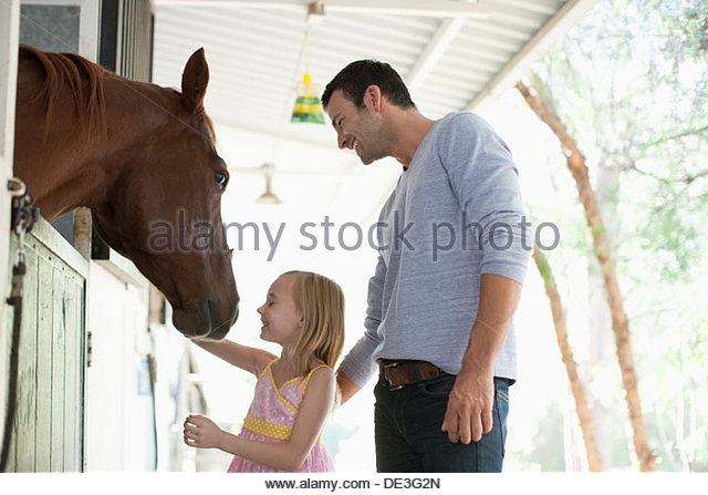 Father and daughter petting horse - Stock Image