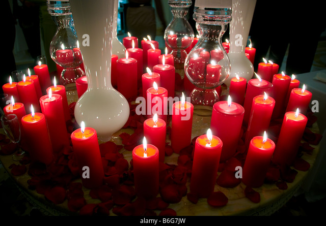 Lit red candles on table. - Stock Image