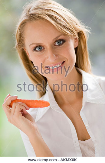 Blonde girl holding carrot - Stock Image
