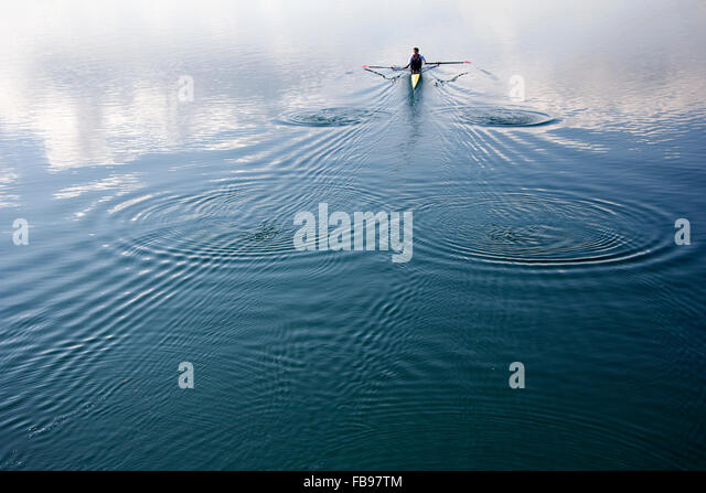 Young man in a boat, rowing on the tranquil lake - Stock-Bilder