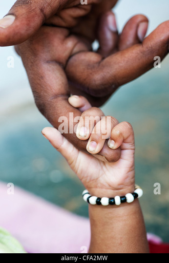 Indian mans hand holding his new born babies hand. Andhra Pradesh, India - Stock Image