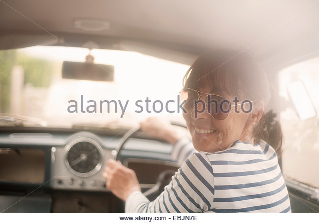 Woman driving a car, smiling - Stock Image