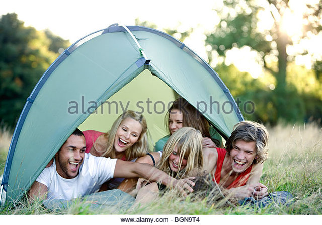 A group of young people in a tent, laughing - Stock Image
