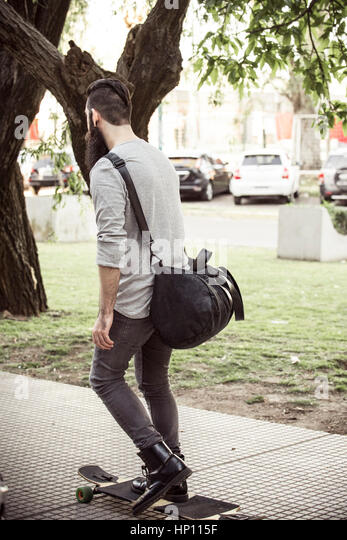 Man longboarding on sidewalk - Stock Image