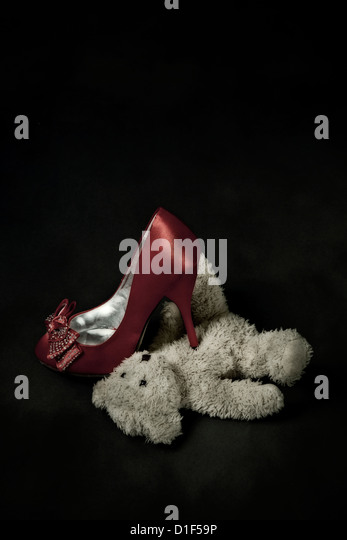 red shoe steps on a teddy bear - Stock Image