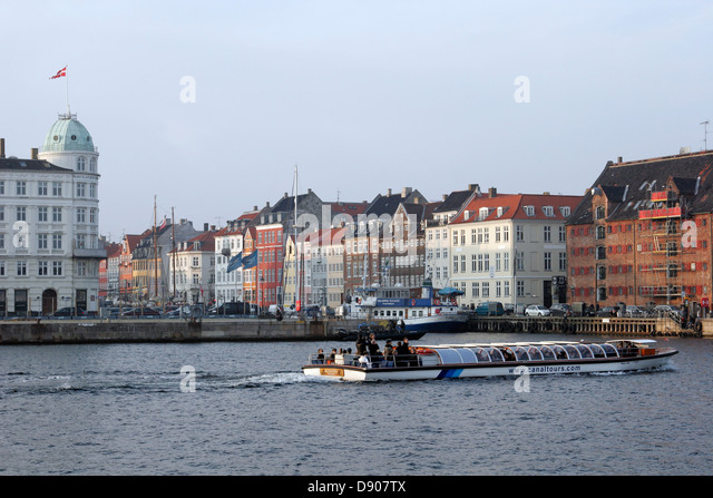 Tourist boat in front of the Nyhavn harbor, Copenhagen, Denmark - Stock Image