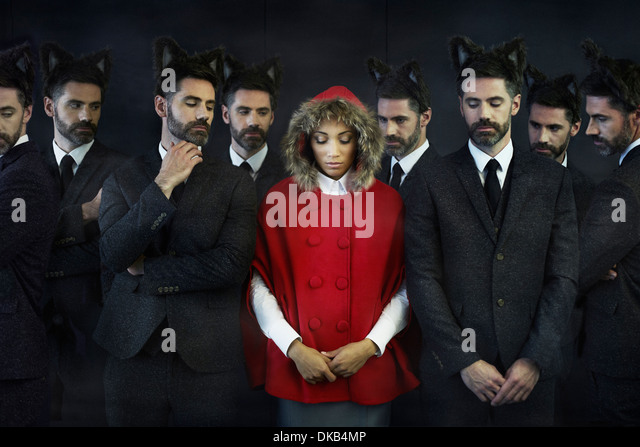 Woman dressed as little red riding hood with businessmen, multiple image - Stock Image