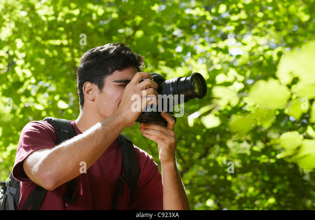 young hispanic man trekking among trees and taking pictures with dslr camera. Horizontal shape, side view, copy - Stock Image